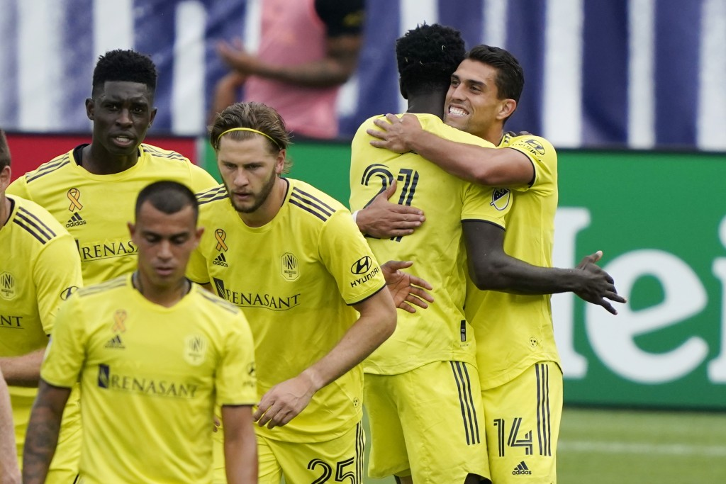 Nashville forward Daniel Rios (14) is congratulated by Derrick Jones (21) after Rios scored a goal against the Houston Dynamo during the second half o...