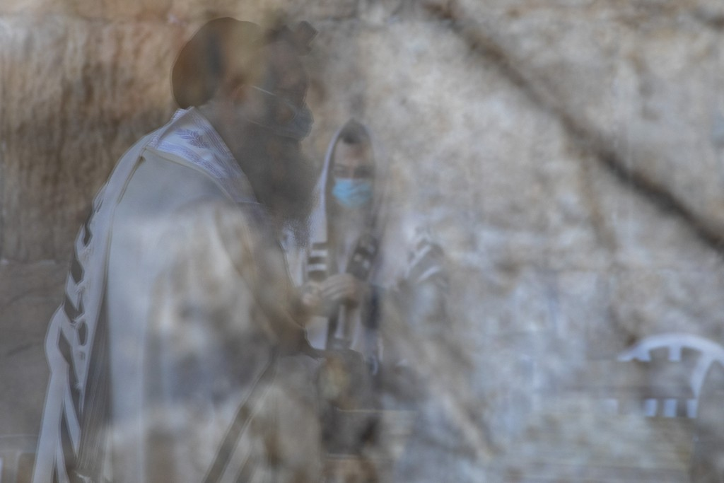 Ultra-Orthodox Jewish men wearing face masks, are reflected on a door window, as they pray ahead of Yom Kippur, the holiest day in the Jewish year whi...