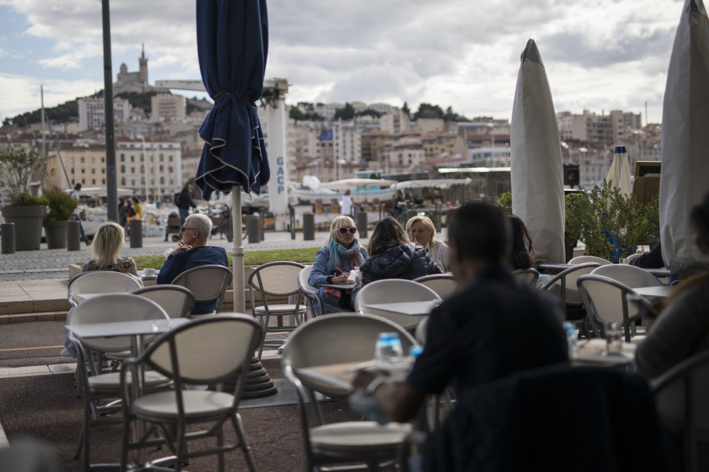 People enjoy refreshments at a restaurant, in Marseille, southern France, Sunday Sept. 27, 2020. As restaurants and bars in Marseille prepared Sunday ...