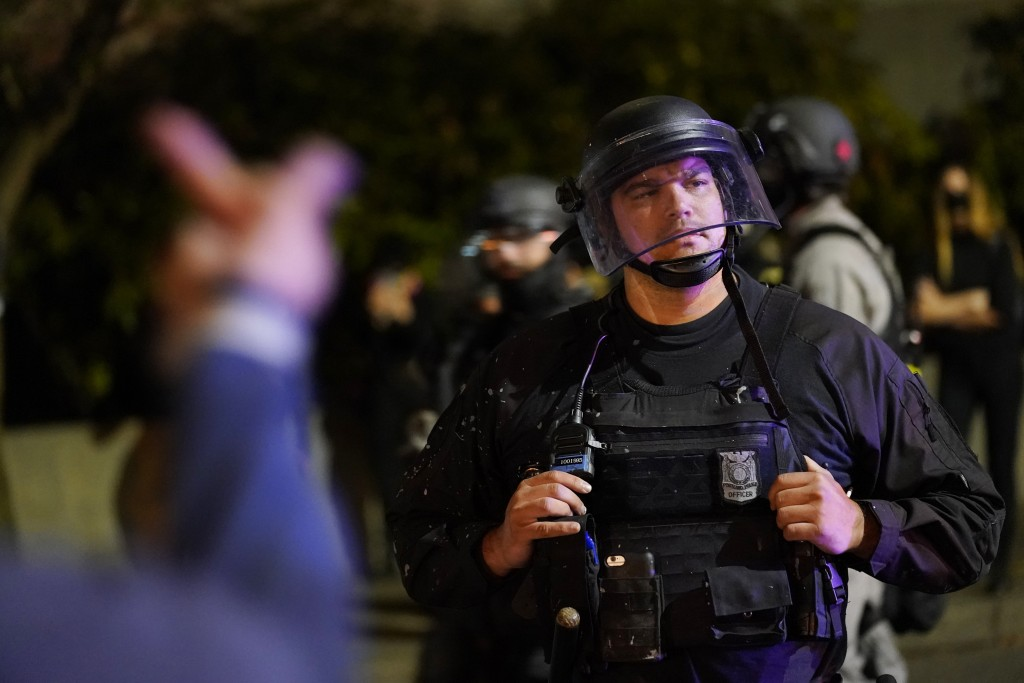 A protestor reacts towards a Portland police officer during protests, Saturday, Sept. 26, 2020, in Portland. The protests which began since the police...