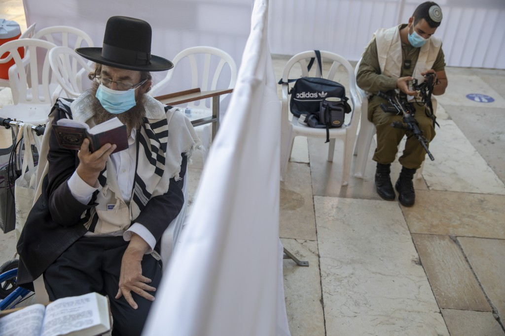 With social distancing barrier, an ultra-Orthodox Jewish man and an Israeli soldier pray ahead of Yom Kippur, the holiest day in the Jewish year which...