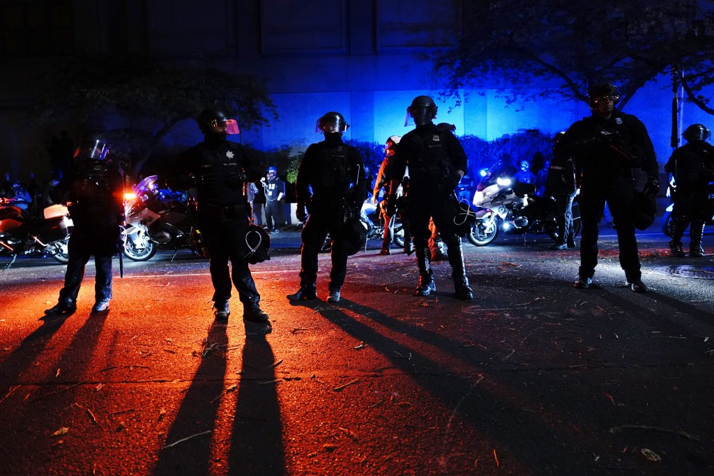 Portland police stand in a street during protests, Saturday, Sept. 26, 2020, in Portland. The protests which began since the police killing of George ...