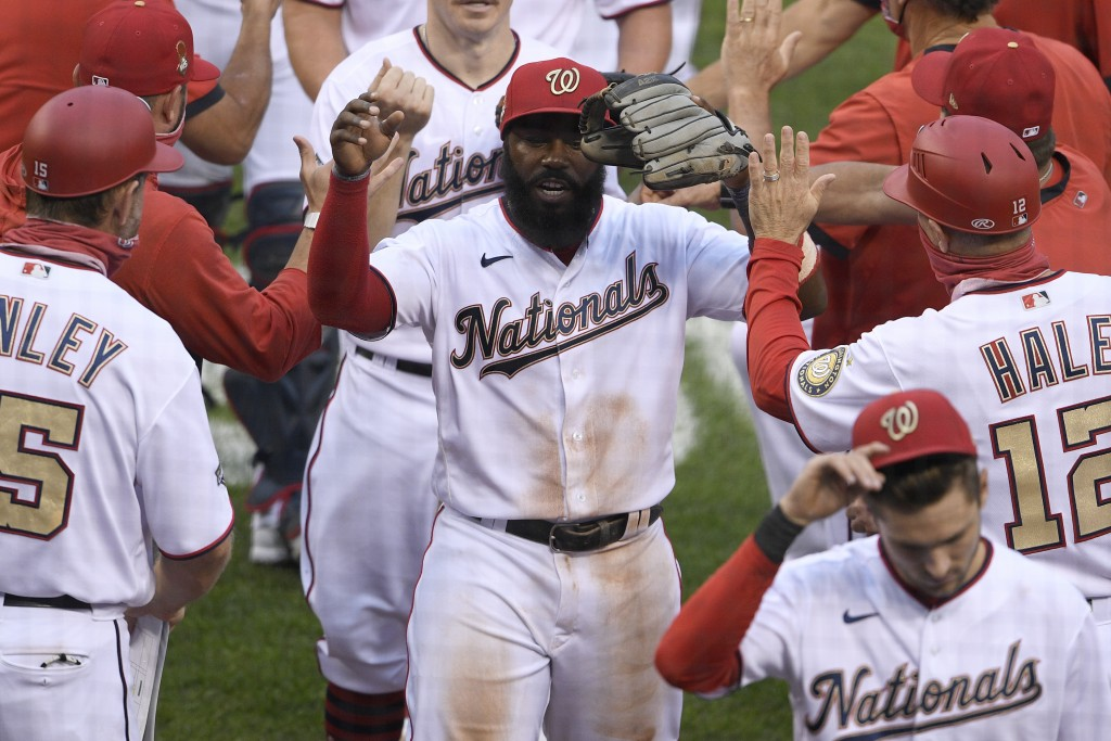 Washington Nationals' Josh Harrison, center, celebrates after the first baseball game of a doubleheader against the New York Mets, Saturday, Sept. 26,...