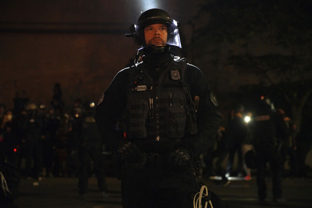 A Portland Police officer stands watching while proesters rally at the Mark O. Hatfield United States Courthouse on Saturday, Sept. 26, 2020, in Portl...