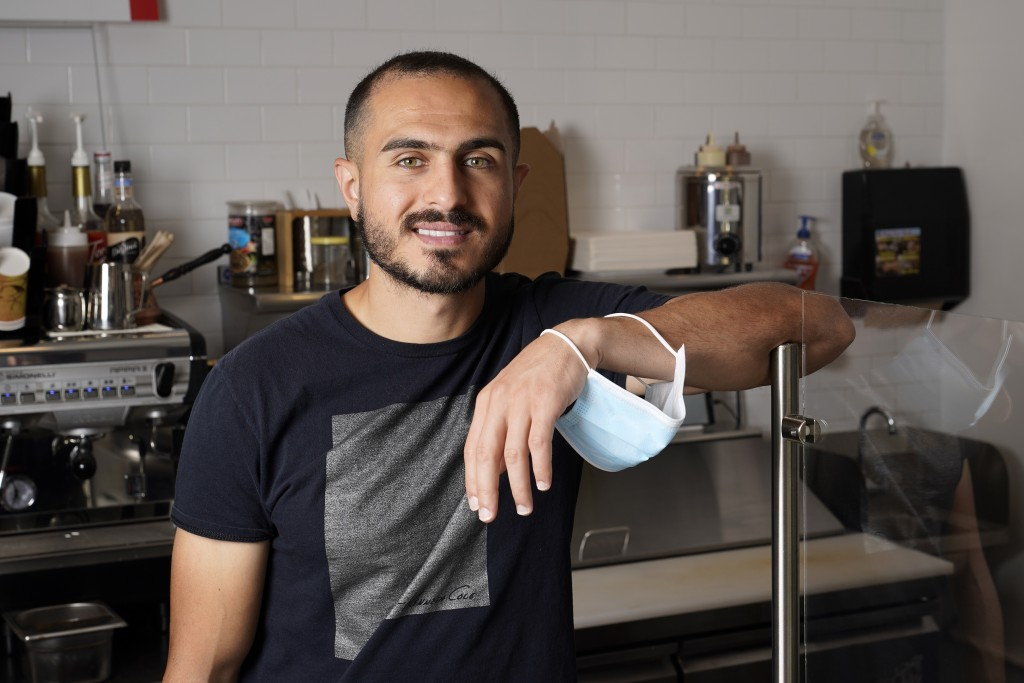 """New U.S. citizen Jad """"Jay"""" Jawad, owner of the Crepe House Cafe, who came to the U.S. as a refugee from war-torn Iraq, poses for a picture in his cafe..."""