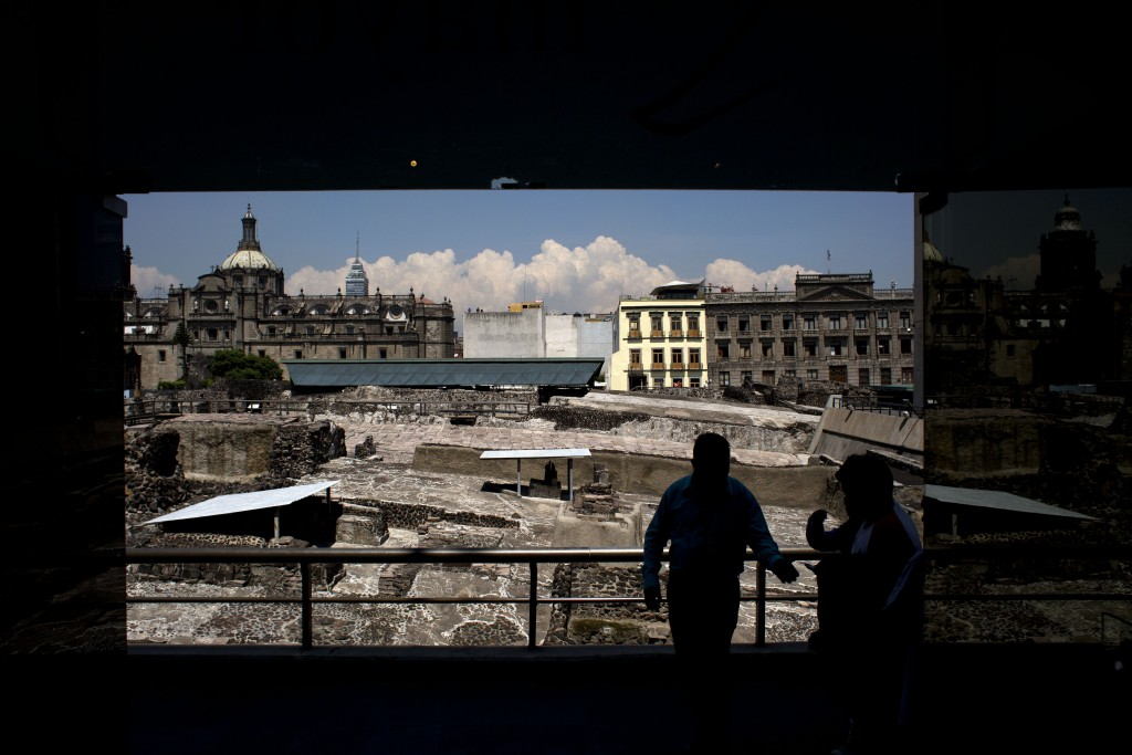 FILE - In this Friday, Aug. 7, 2015 file photo, a worker stands in front of ongoing excavations at the Templo Mayor archeological site, directing peop...