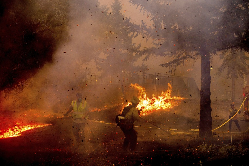 Firefighters work to save the Louis Stralla Water Treatment Plant as the Glass Fire burns in St. Helena, Calif., Sunday, Sept. 27, 2020. (AP Photo/Noa...