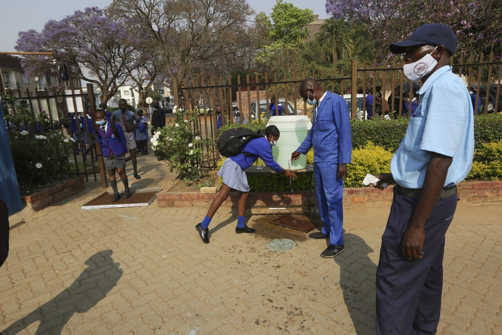 A child washes her hands before entering school in Harare, Zimbabwe, Monday Sept, 28, 2020. Zimbabwe schools have reopened in phases, but with smaller...