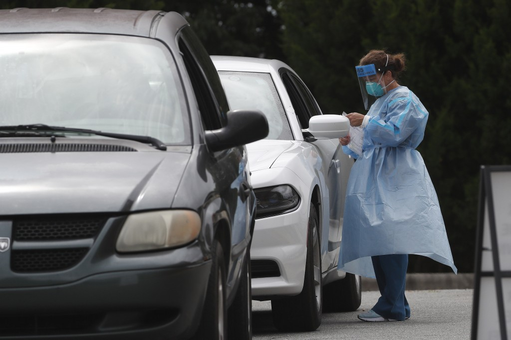 FILE - In this July 9, 2020, file photo cars line up at a community coronavirus testing site operated by Cone Health and the county Health Department ...