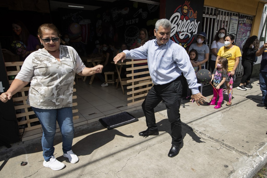 Fabio Rodolfo Vasquez dances with a customer at a promotional event outside a coffee shop on the outskirts of Guatemala City, Saturday, Sept. 19, 2020...