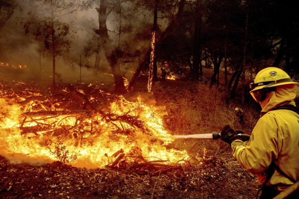 A firefighter battles the Glass Fire burning in Calistoga, Calif., on Sunday, Sept. 27, 2020. (AP Photo/Noah Berger)