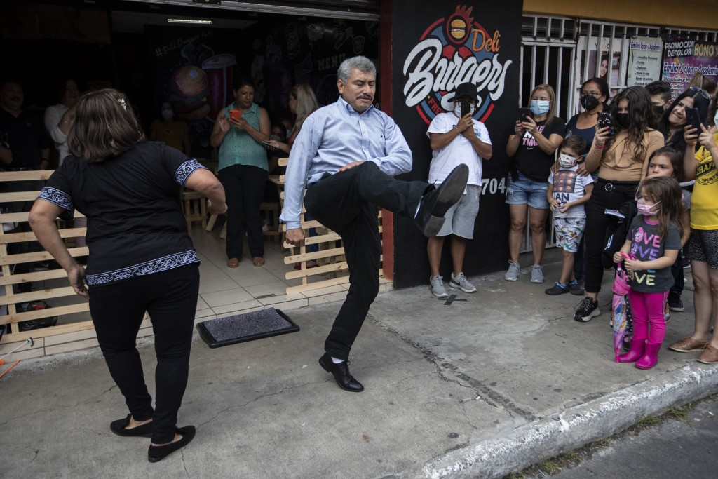 Fabio Rodolfo Vasquez, center, and his wife, Maria Moreno, dance at a promotional event outside a coffee shop, on the outskirts of Guatemala City, Sat...