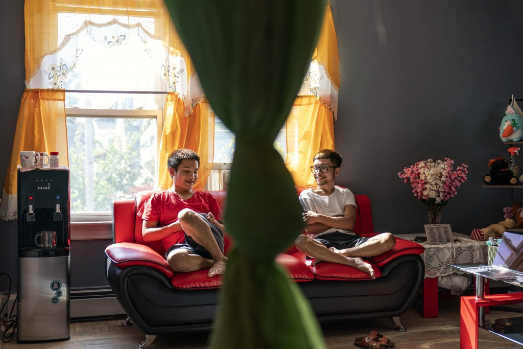 Bawi UK, 22, right, chats with his brother, Leng Nung, 20, in the apartment they share in Providence, R.I., Saturday, Sept. 26, 2020. UK was a small c...