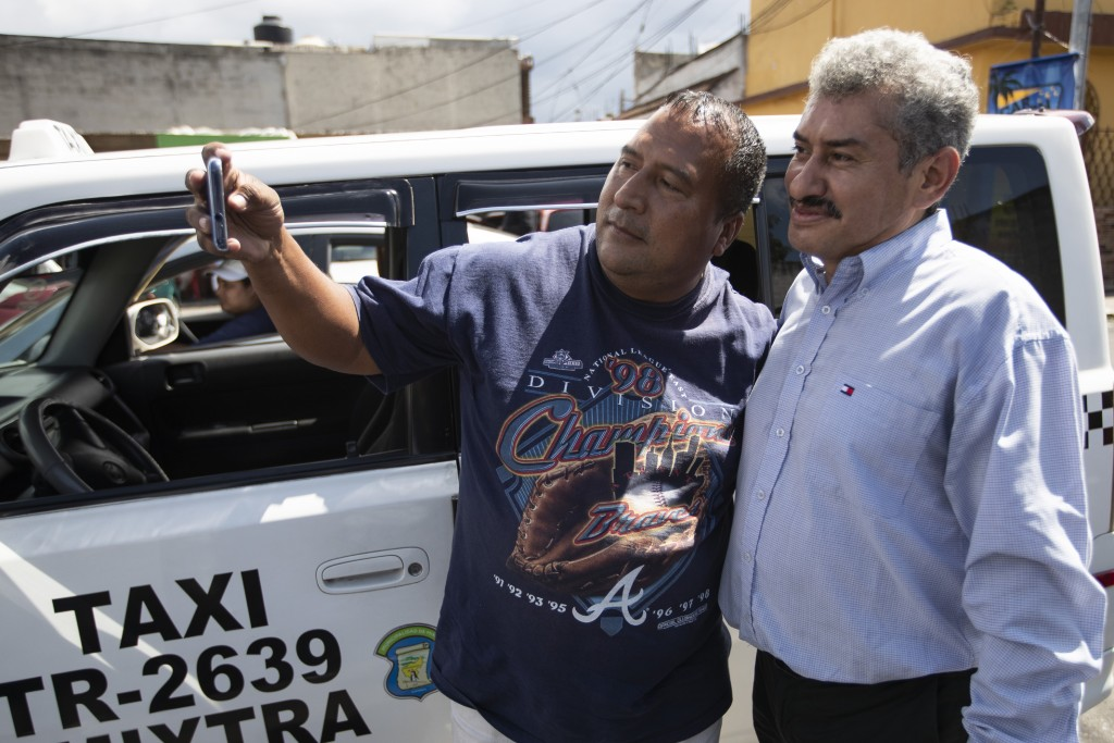 Fabio Rodolfo Vasquez, right, poses with a fan at a promotional event outside a coffee shop, on the outskirts of Guatemala City, Saturday, Sept. 19, 2...