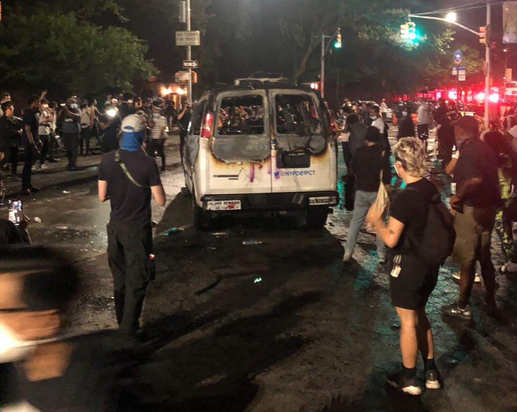 FILE - In this May 29, 2020 file photo, protesters stand near a burned New York City Police Department van in the Brooklyn borough of New York. Recent...