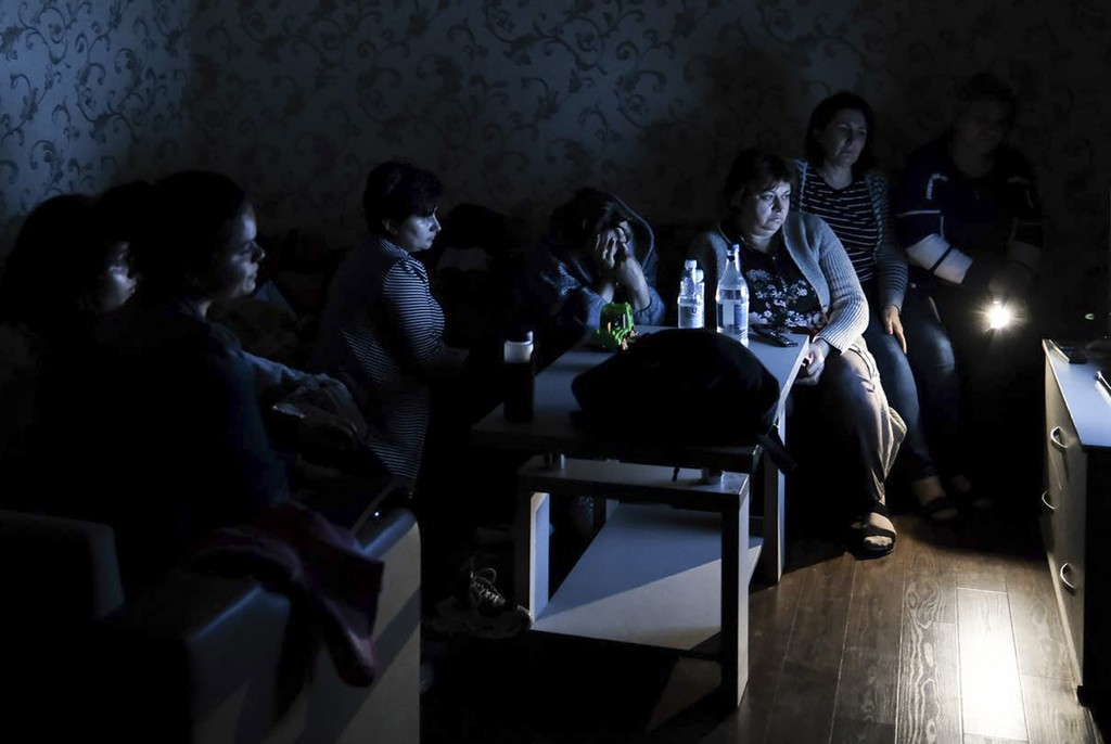 In this handout photo released by the Armenian Foreign Ministry on Monday, Sept. 28, 2020, people watch the State TV as they gather in a bomb shelter ...