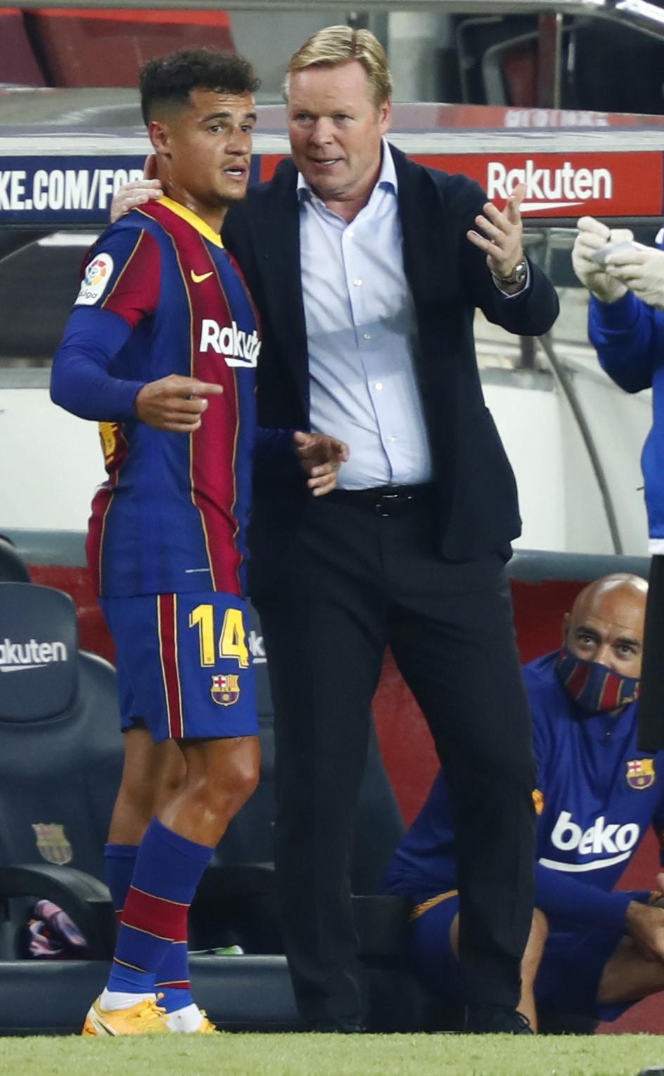 Barcelona's head coach Ronald Koeman speaks with Barcelona's Philippe Coutinho during the Spanish La Liga soccer match between FC Barcelona and Villar...