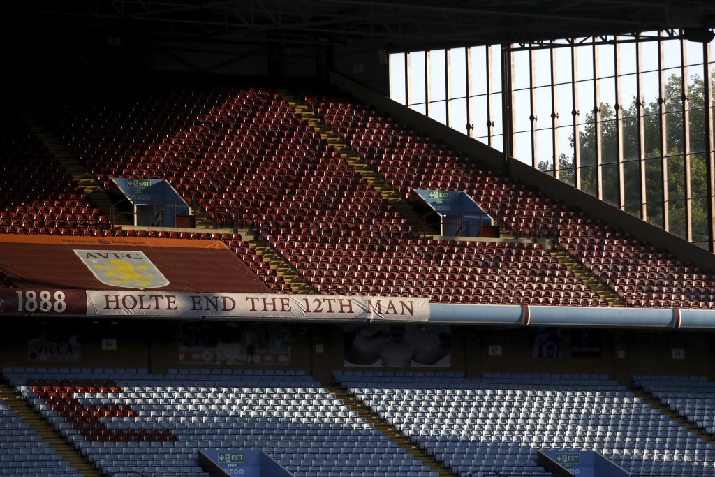 FILE - In this Monday, Sept. 21, 2020 file photo, the sun illuminates the empty stands before the English Premier League soccer match between Aston Vi...