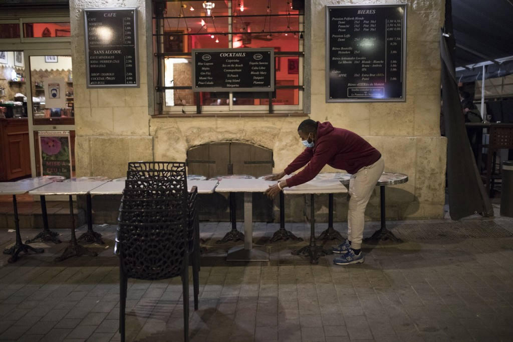 A waiter closes a bar terrace in Marseille, southern France, late Sunday Sept. 27, 2020. As restaurants and bars in Marseille prepared Sunday to shut ...