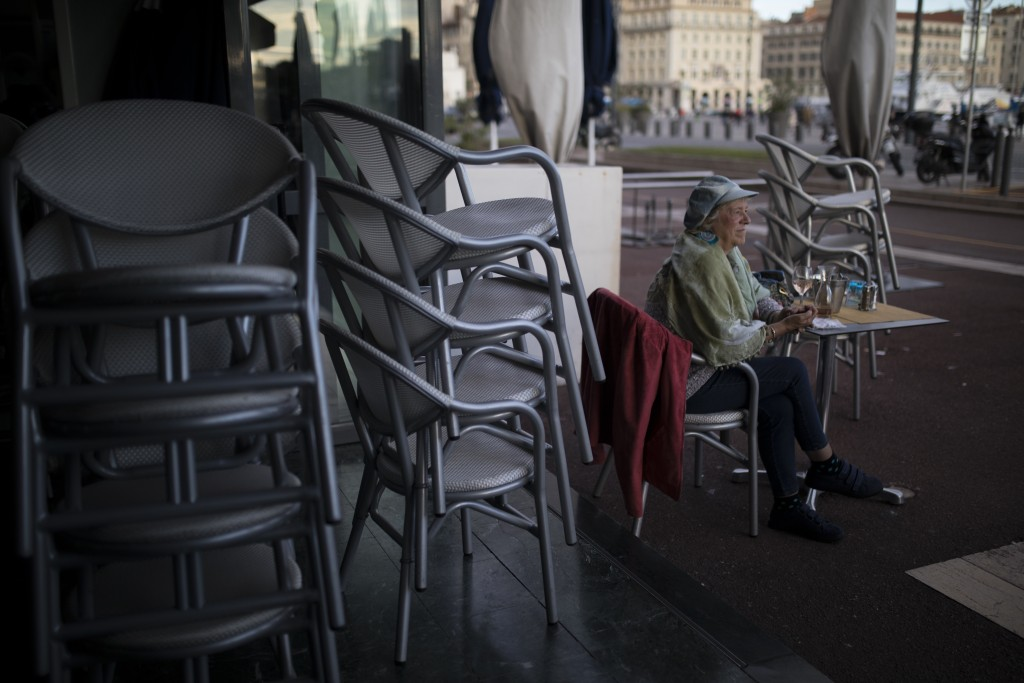 A customer sitss at a restaurant as it closes in Marseille, southern France, Sunday Sept. 27, 2020. As restaurants and bars in Marseille prepared Sund...