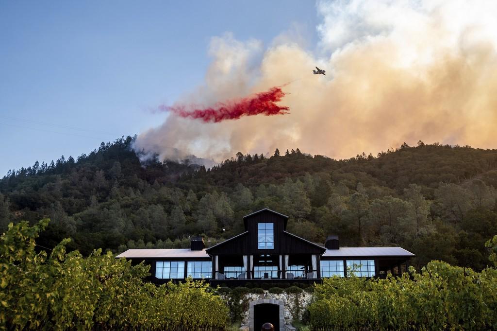An air tanker drops retardant on the Glass Fire burning above Davis Estates winery in Calistoga, Calif., on Sunday, Sept. 27, 2020. (AP Photo/Noah Ber...