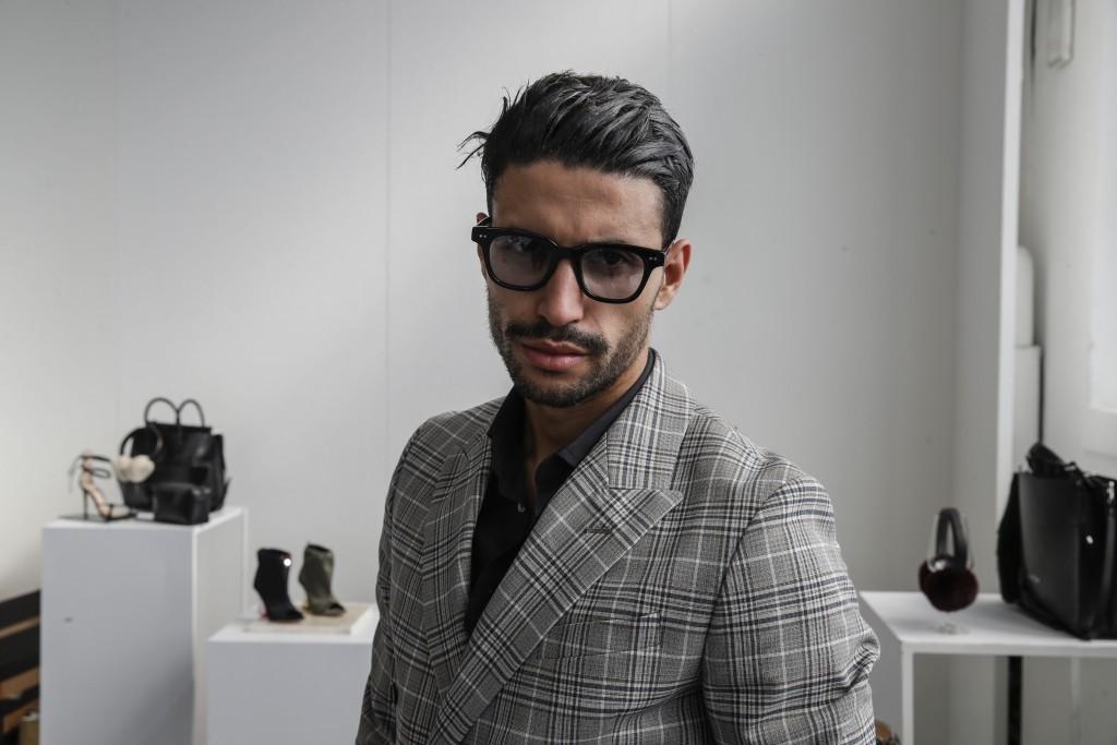 Fashion designer Karim Daoudi poses in front of his creations, in Milan, Italy, Sunday, Sept. 27, 2020. (AP Photo/Luca Bruno).