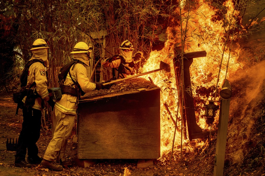Firefighters knock down flames on a dog house while battling the Glass Fire burning in St. Helena, Calif., on Sunday, Sept. 27, 2020. (AP Photo/Noah B...