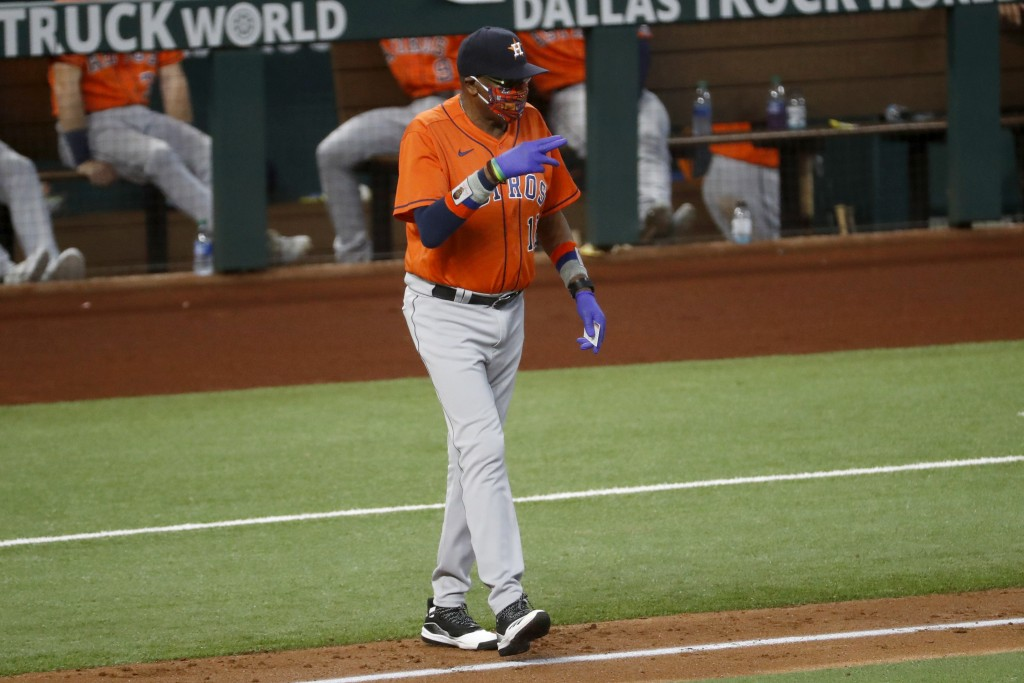 Houston Astros manager Dusty Baker Jr. signals as he walks to the mound to change pitchers during the fourth inning of a baseball game against the Tex...