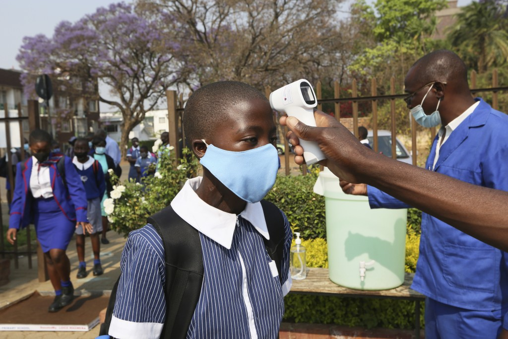 A child gets her temperature checked before entering school in Harare, Zimbabwe, Monday, Sept, 28, 2020. Zimbabwe schools have reopened in phases, but...