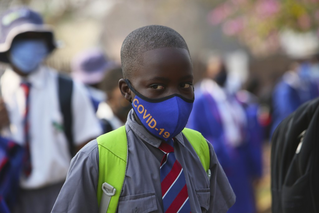A child wearing a mask queues outside school in Harare, Zimbabwe, Monday, Sept, 28, 2020. Zimbabwe schools have reopened in phases, but with smaller n...