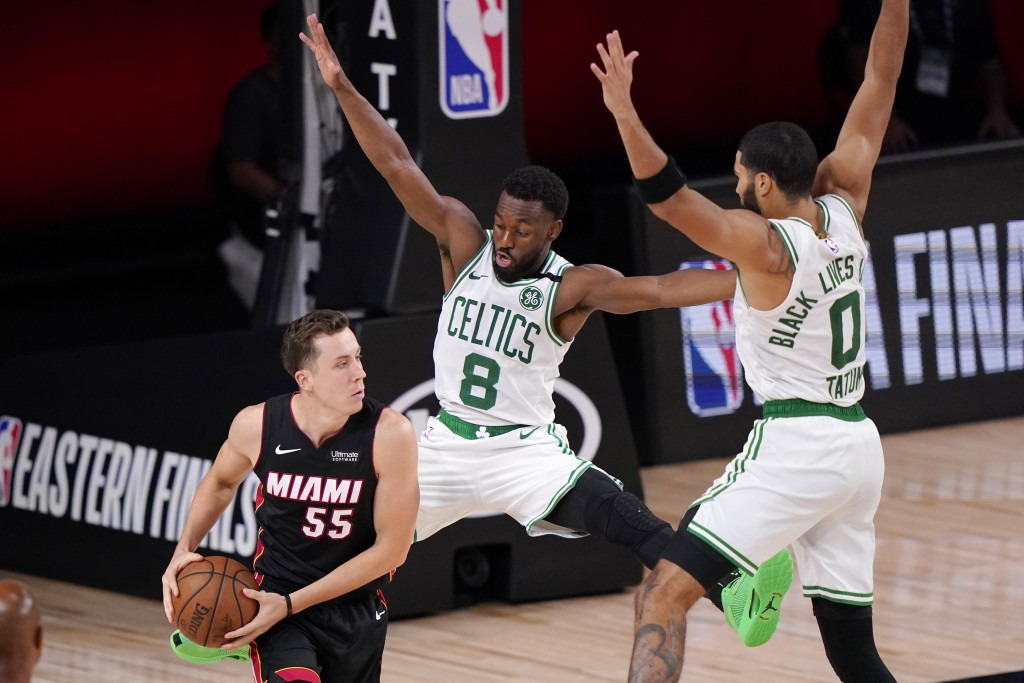 Miami Heat's Duncan Robinson (55) looks for help as Boston Celtics' Kemba Walker (8) and teammate Jayson Tatum (0) defend during the second half of an...