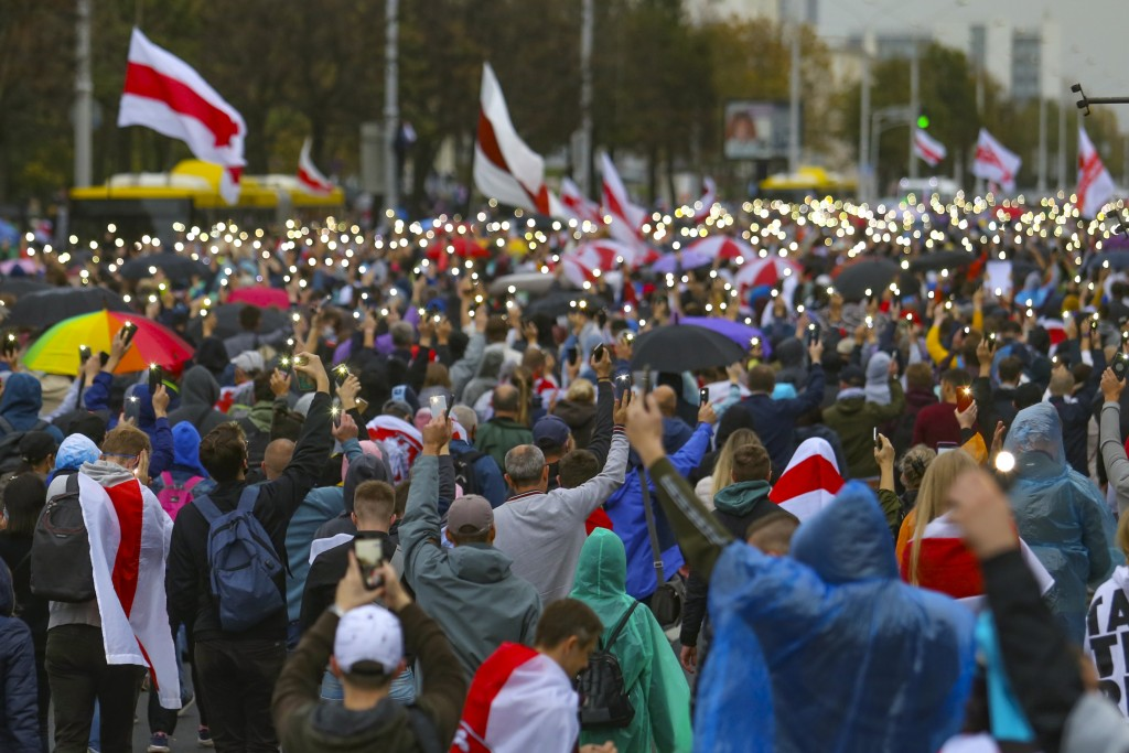 Demonstrators light their cell phones during an opposition rally to protest the official presidential election results in Minsk, Belarus, Sunday, Sept...