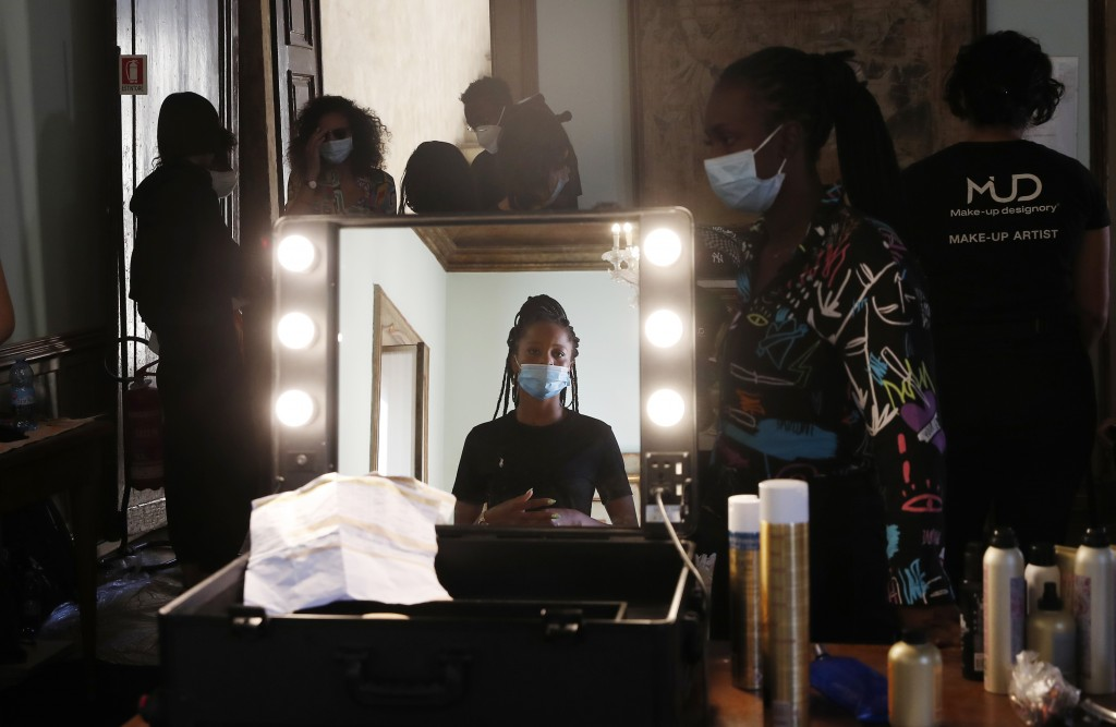 """An hairdresser is reflected in a mirror as she waits in the backstage at the """"We are Made in Italy - Black Lives Matter in Italian fashion Collection""""..."""
