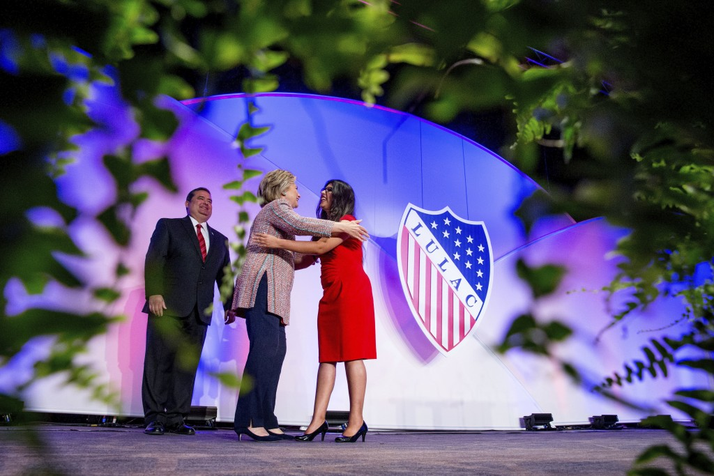 In this July 14, 2016 photo Democratic presidential candidate Hillary Clinton, accompanied by then-LULAC President Roger C. Rocha, Jr., left, hugs Uni...