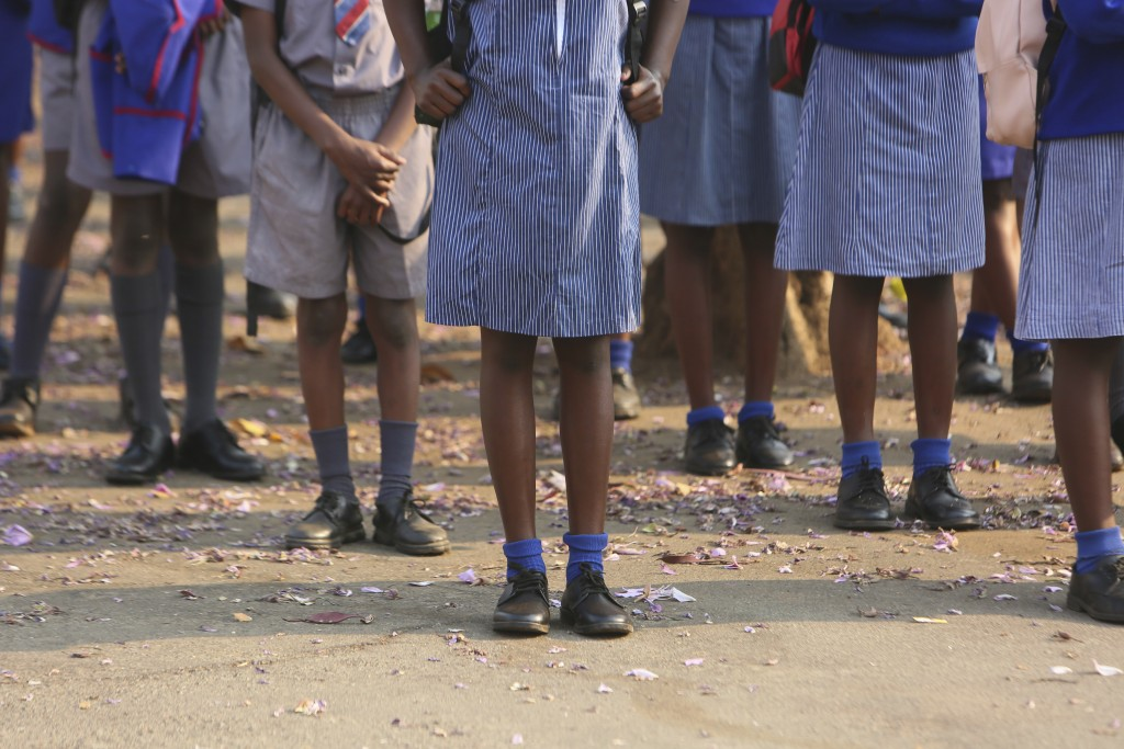 Schoolchildren queue outside their school in Harare, Zimbabwe, Monday, Sept, 28, 2020. Zimbabwe schools have reopened in phases, but with smaller numb...