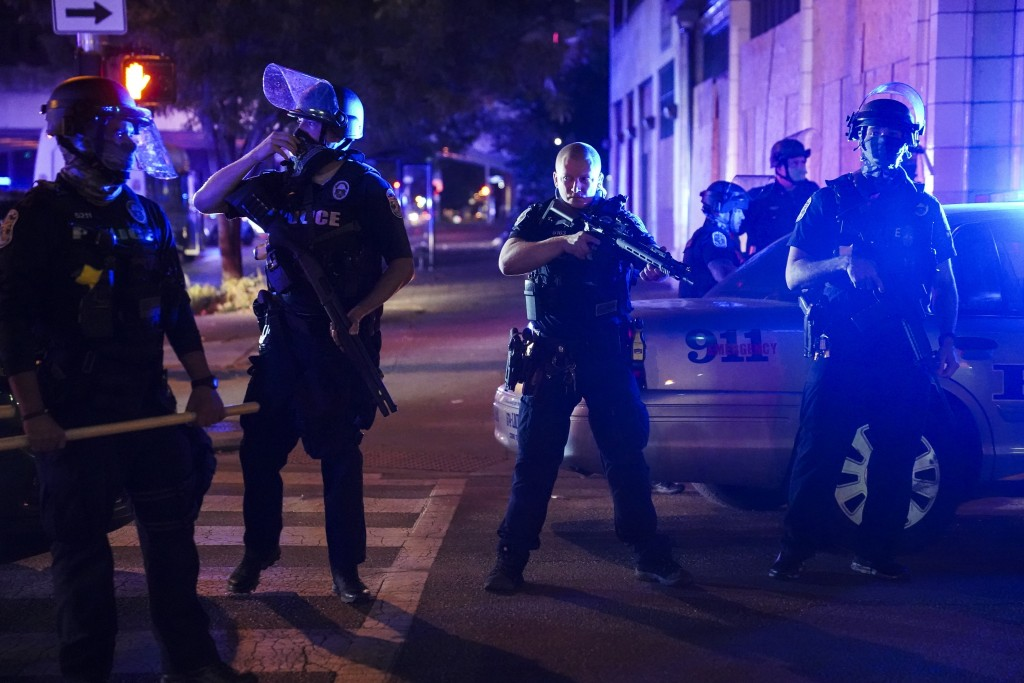 FILE - Police stand guard on the perimeter of a crime scene after a police officer was shot, Wednesday, Sept. 23, 2020, in Louisville, Ky. Recent shoo...