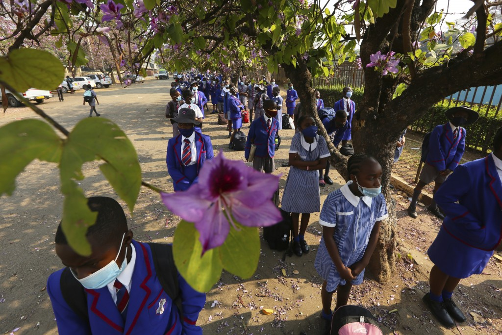 Schoolchildren wait to enter their school in Harare, Zimbabwe, Monday Sept, 28, 2020. Zimbabwe schools have reopened in phases, but with smaller numbe...