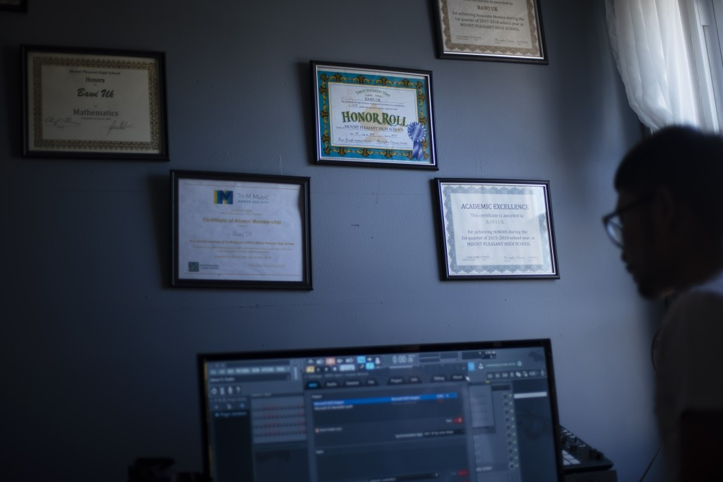 An Honor Roll certificate hangs on the bedroom wall of Bawi UK, 22, at his home in Providence, R.I., Saturday, Sept. 26, 2020. UK was a small child wh...