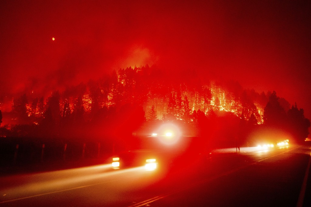 An emergency vehicle drives along Silverado Trail as the Glass Fire burns in St. Helena, Calif., Sunday, Sept. 27, 2020. (AP Photo/Noah Berger)