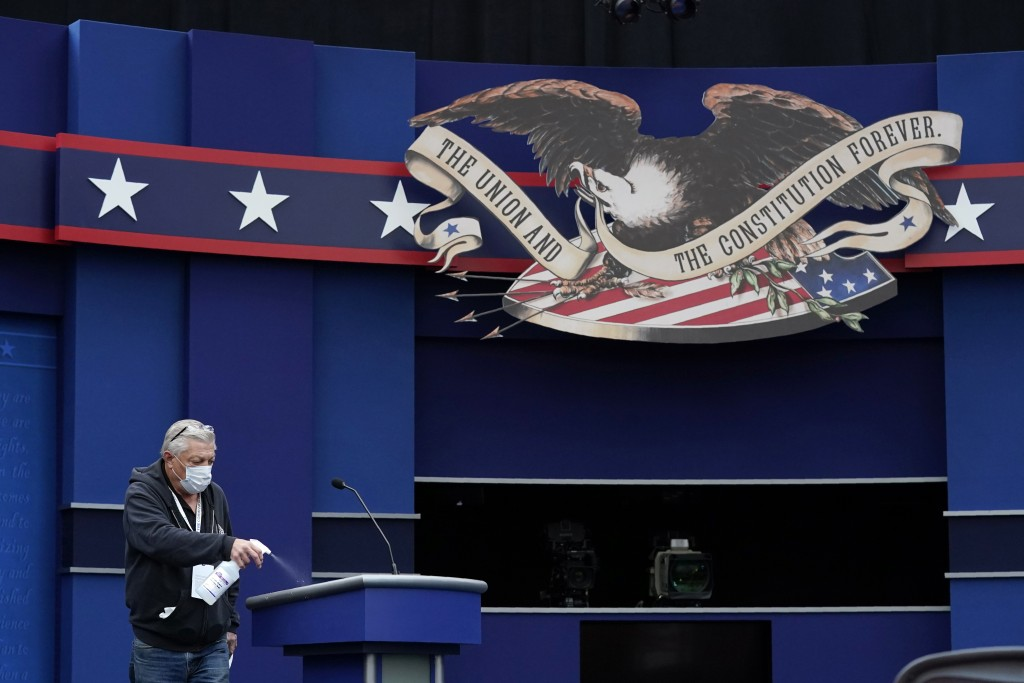 A worker sprays sanitizer on a lectern as preparations take place for the first Presidential debate in the Sheila and Eric Samson Pavilion, Monday, Se...