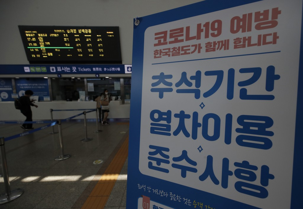 """Passengers arrive to buy train tickets near a banner reading """"Notice to use the train during the Chuseok holiday. Prevention of COVID-19"""" at the Seoul..."""