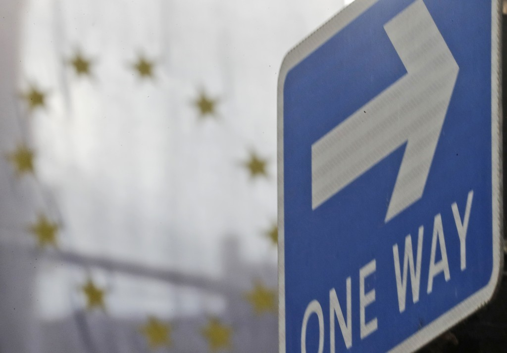 The EU flag hangs from Europa House behind a signpost in London, Tuesday, Sept. 29, 2020. Britain has entered a crucial week of post-Brexit talks with...