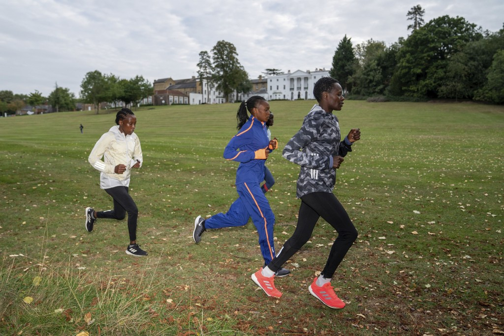 In this image issued by London Marathon Events, Kenya's Edith Chelimo, right, trains in the grounds of the official hotel and biosecure bubble in Lond...