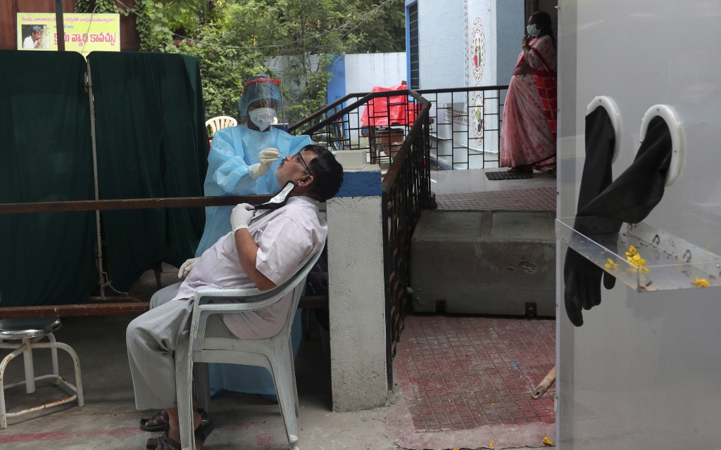 A health worker takes a nasal swab sample to test for COVID-19 in Hyderabad, India, Tuesday, Sept. 29, 2020. India confirmed coronavirus tally has rea...