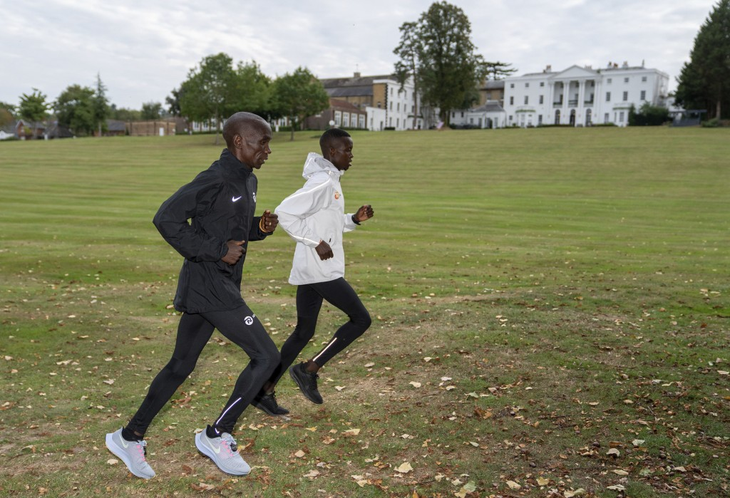 In this image issued by London Marathon Events, Kenya's Eliud Kipchoge trains alongside his pacemaker in the grounds of the official hotel and biosecu...