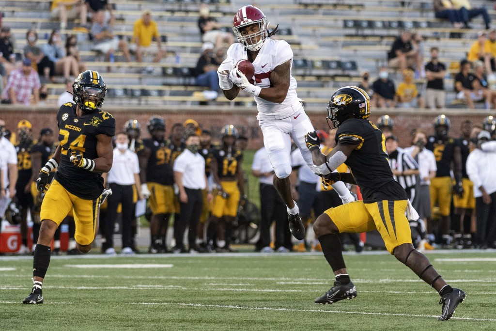 FILE - In this Saturday, Sept. 26, 2020, file photo, Alabama wide receiver Jaylen Waddle, center, pulls down a reception between Missouri's Tyree Gill...