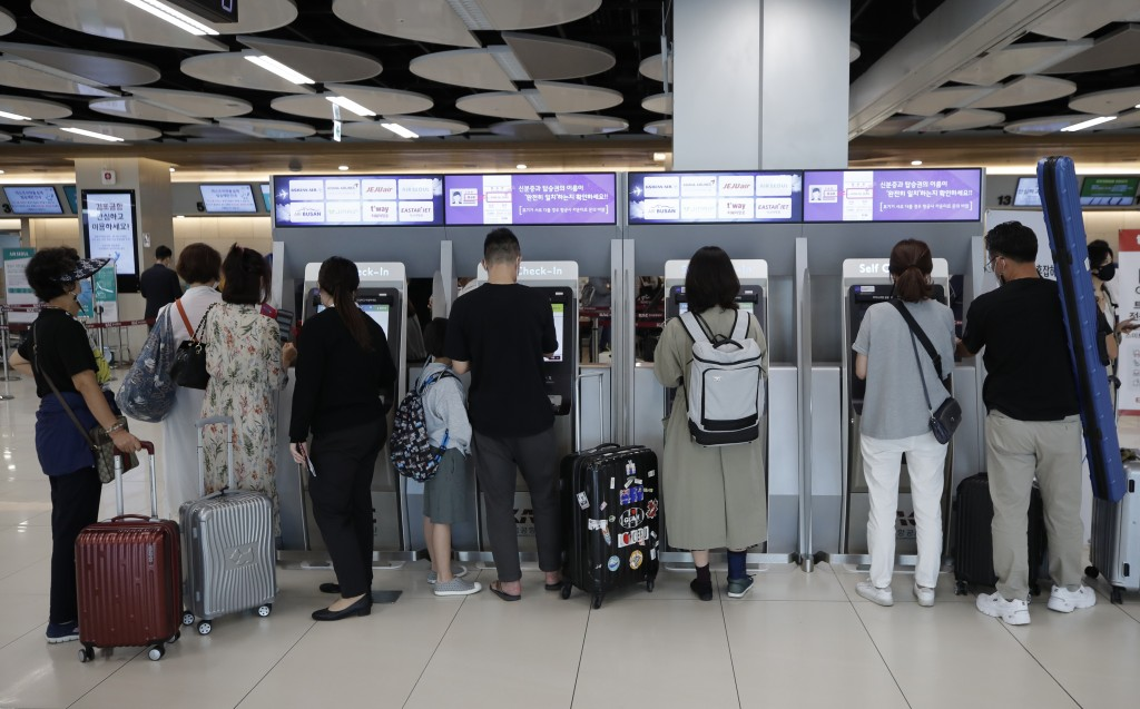 Passengers wearing face masks use the self-check-in machines for their flights ahead of the upcoming Chuseok holiday, the Korean version of Thanksgivi...