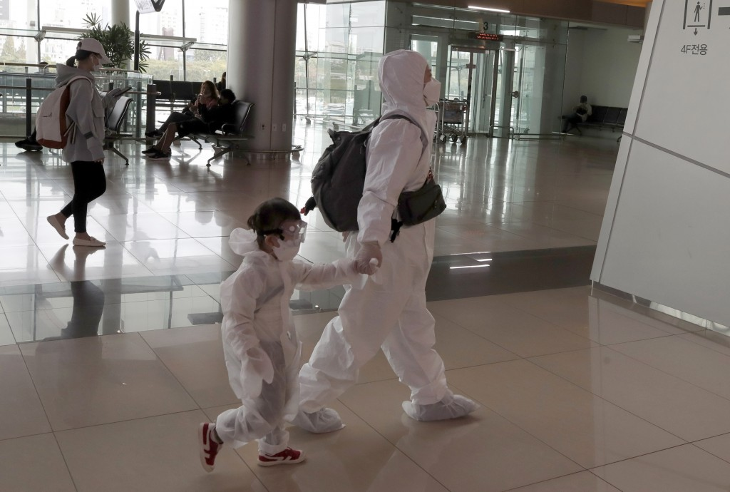 Passengers wearing face masks and protect gears as a precaution against the coronavirus, walk to board their plane ahead of the upcoming Chuseok holid...