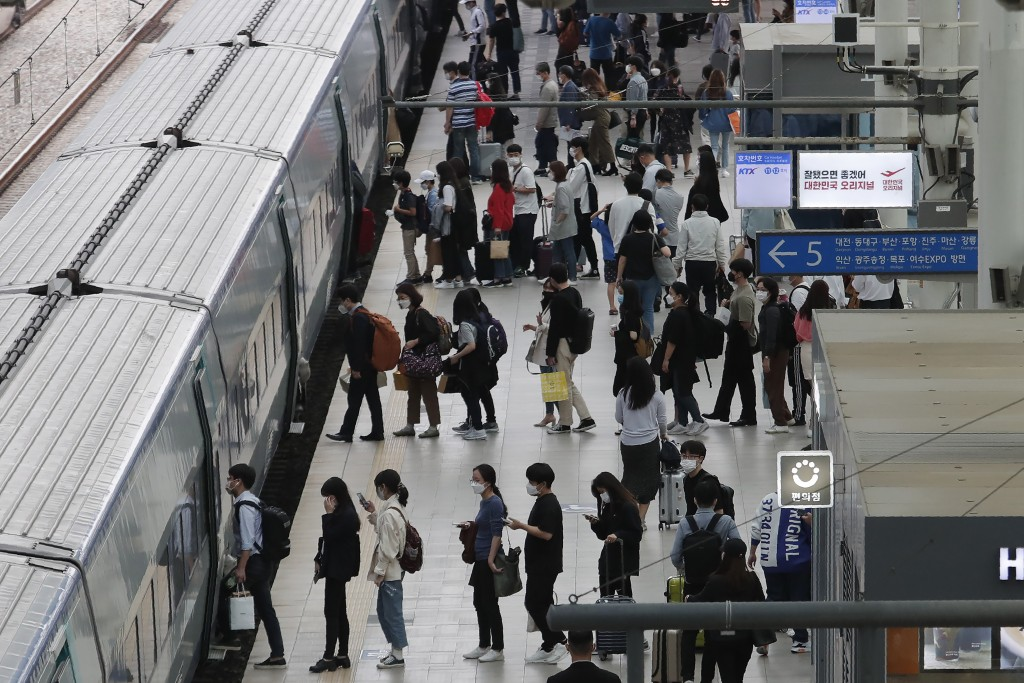 People wearing face masks to help protect against the spread of the coronavirus line up to board a train ahead of the upcoming Chuseok holiday, the Ko...