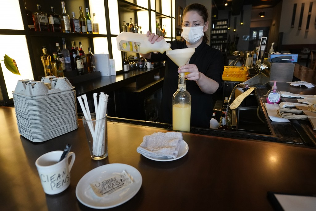 Bartender Devon Schickling prepares lemon juice for drinks, Tuesday, Sept. 29, 2020, at Mama Fox bar and restaurant in the Brooklyn borough of New Yor...